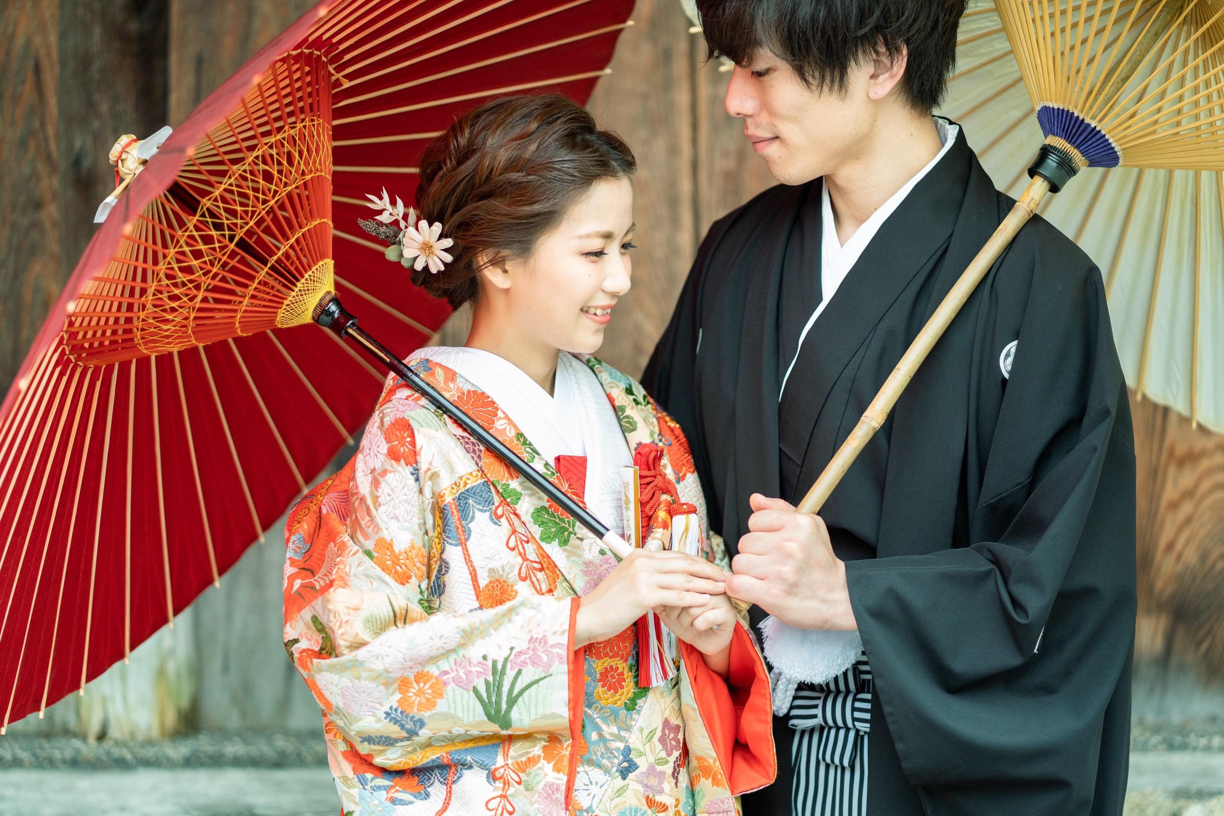 和傘をさしてる新郎新婦