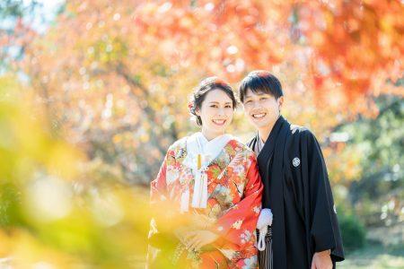 紅葉の中、笑顔の花嫁花婿さん